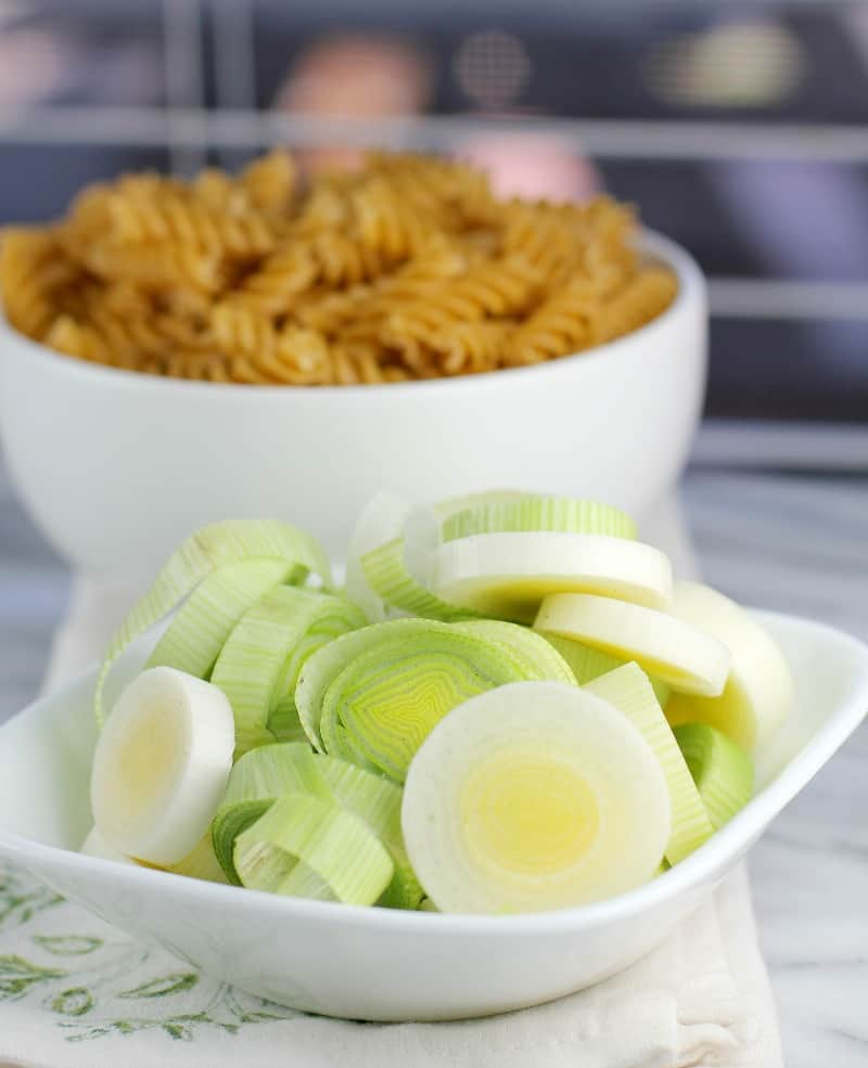 sliced leeks in a small white bowl; uncooked pasta in the background