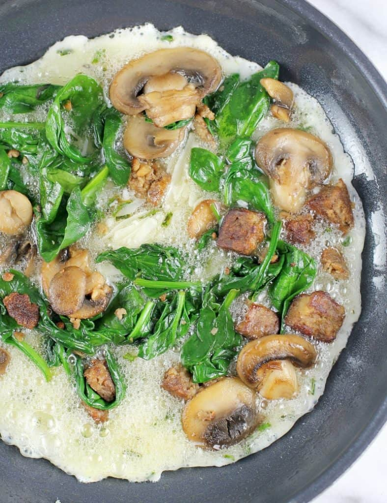 skillet with the egg whites cooking, topped with spinach mushrooms and sausage