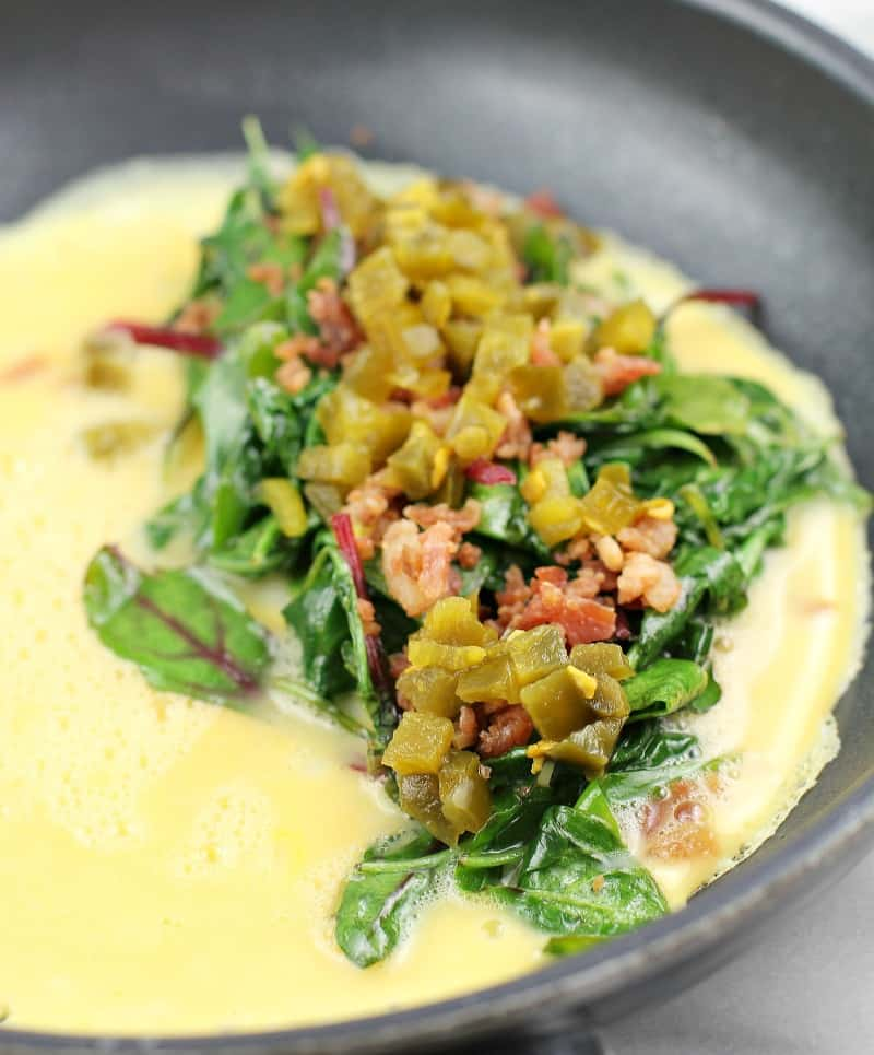 Side view of omelet toppings (greens, bacon, and jalapeno) on egg cooking in skillet.