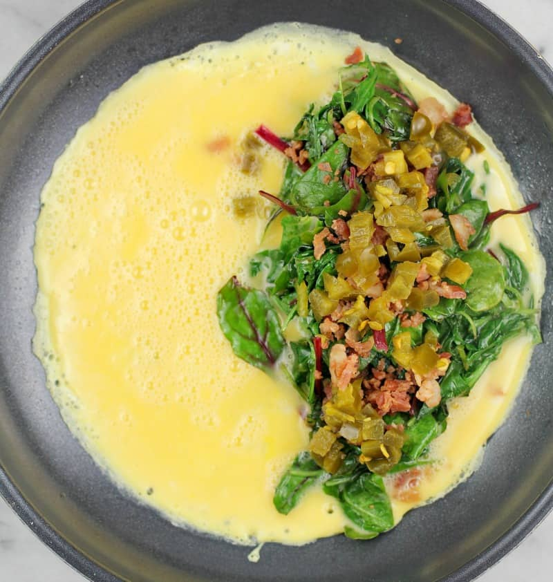 Top down view of omelet toppings (greens, bacon, and jalapeno) on egg cooking in skillet.