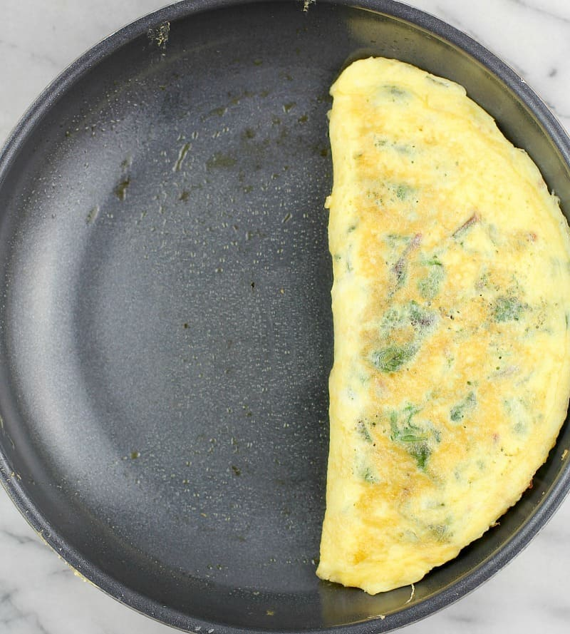 Top down view of the formed and cooked omelet in a skillet