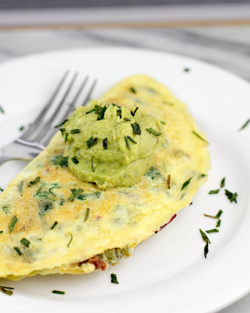 Omelet on white plate, topped with dollop of guacamole, snipped chives sprinkled over. Fork in the background.