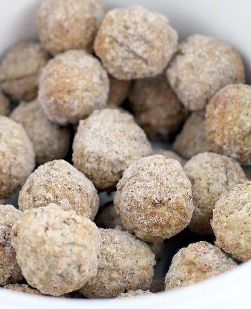 frosty frozen meatballs in a white ceramic crockpot