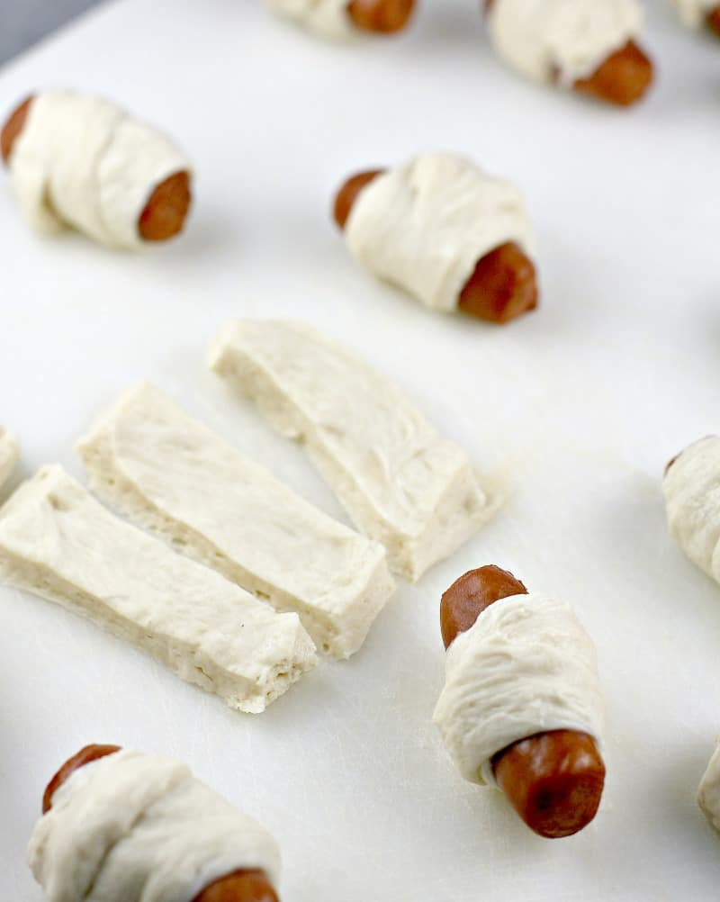 strips of pizza dough with several wrapped mini pigs in blankets on a white board
