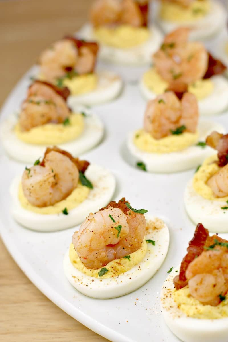 creole shrimp recipe on deviled eggs with bacon on a white platter; parsley sprinkled overtop