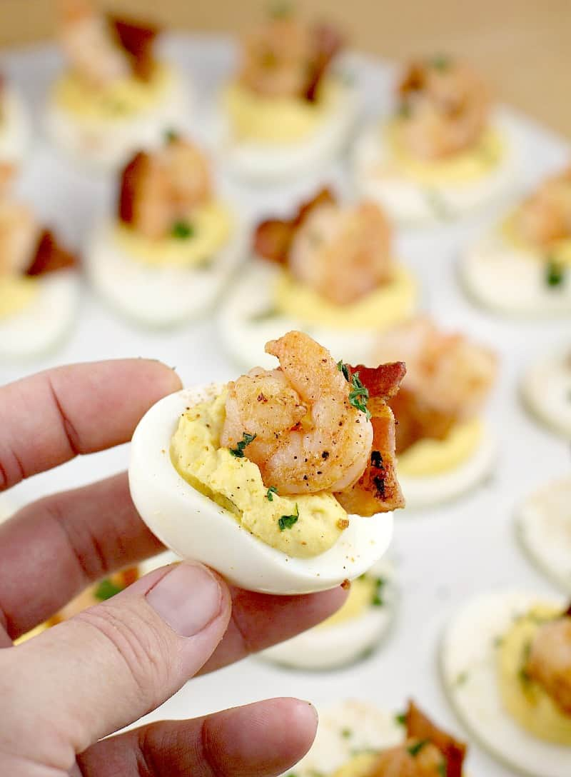a hand holding up one deviled egg with bacon and shrimp; a white platter of others is in the background