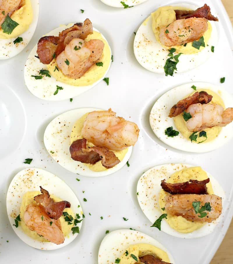 top down view of deviled eggs recipe finished on a white platter with shrimp and bacon on top, garnished with parsley