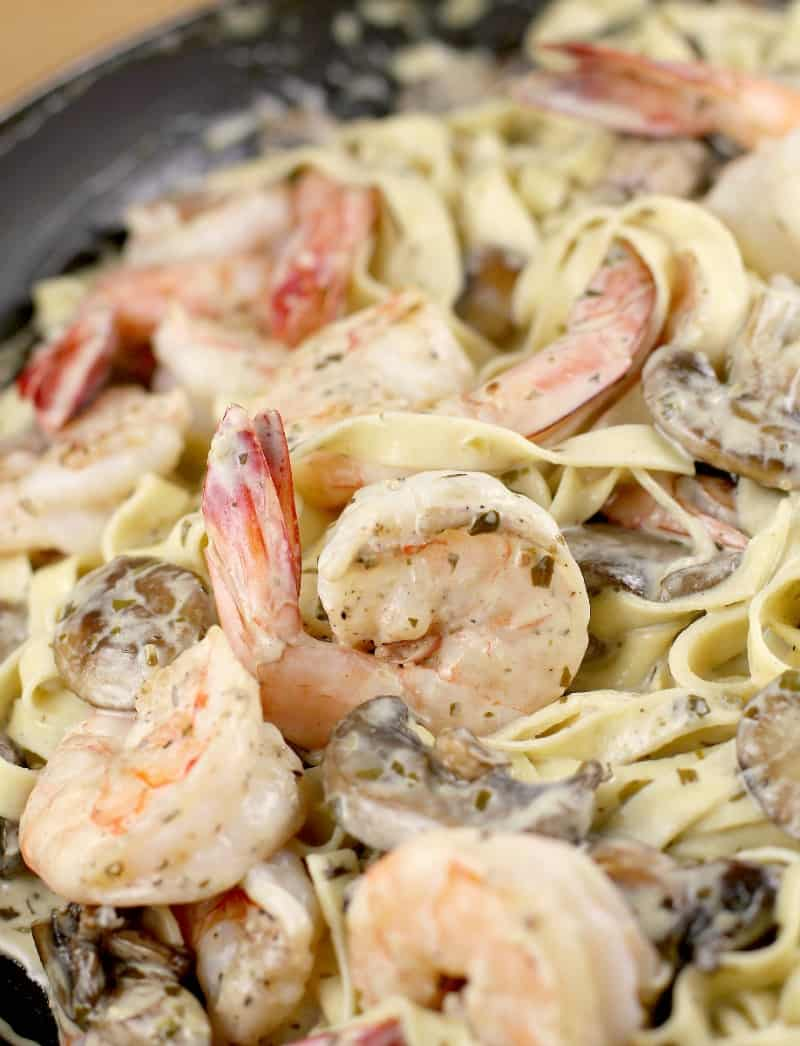 close in view of the shrimp and mushrooms added to the pasta with the pesto sauce in a skillet