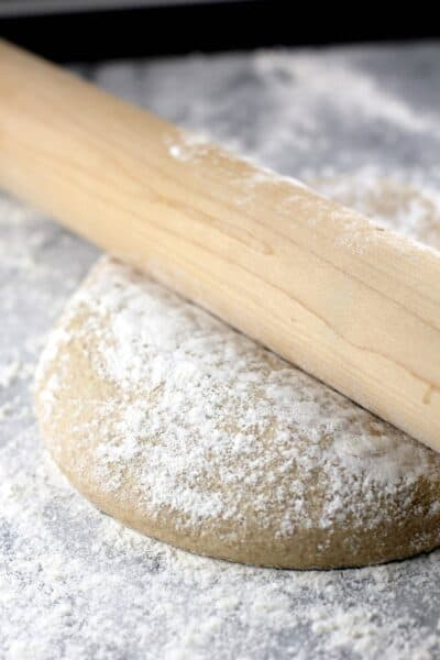 whole wheat pizza dough on a marble surface with a rolling pin
