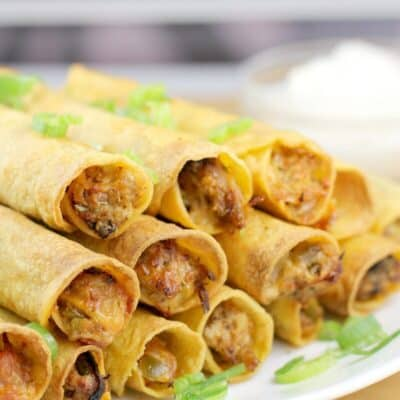 side view of taquitos on a white dish