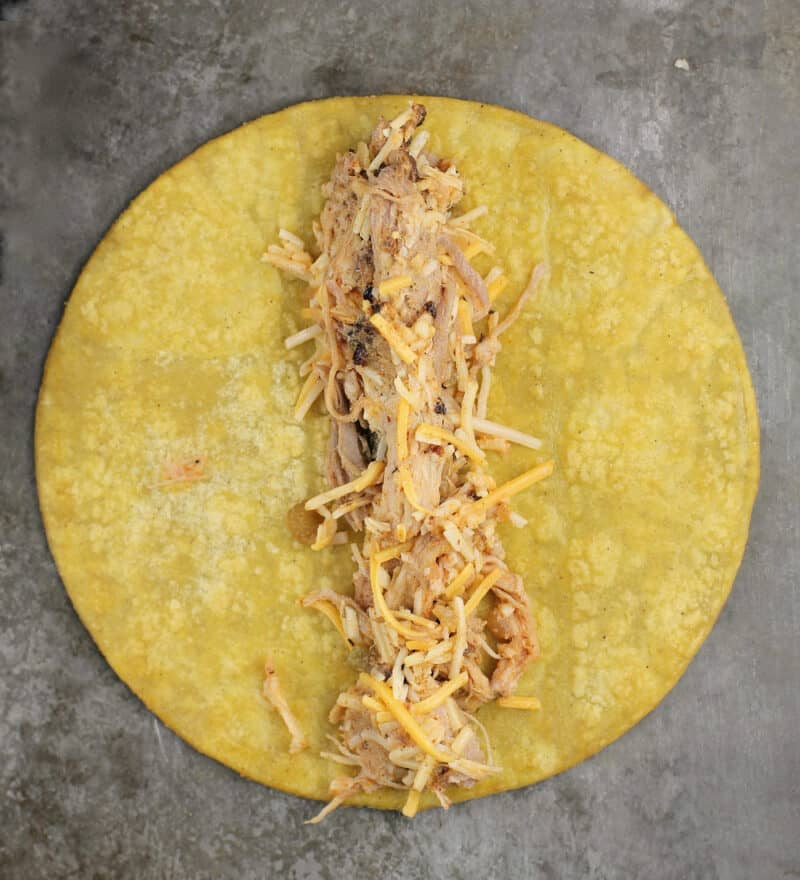 pulled pork filling down the center of a corn tortilla
