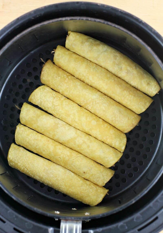 rolled corn tortillas in an air fryer basket
