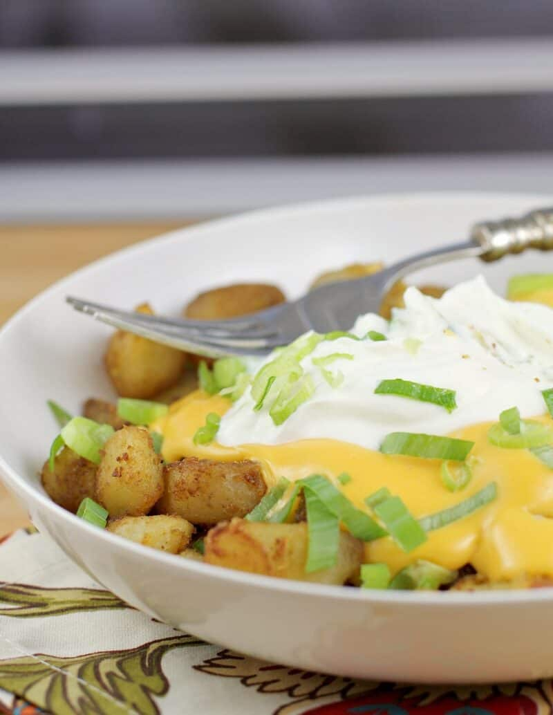 fiesta potatoes in a white bowl with fork on top
