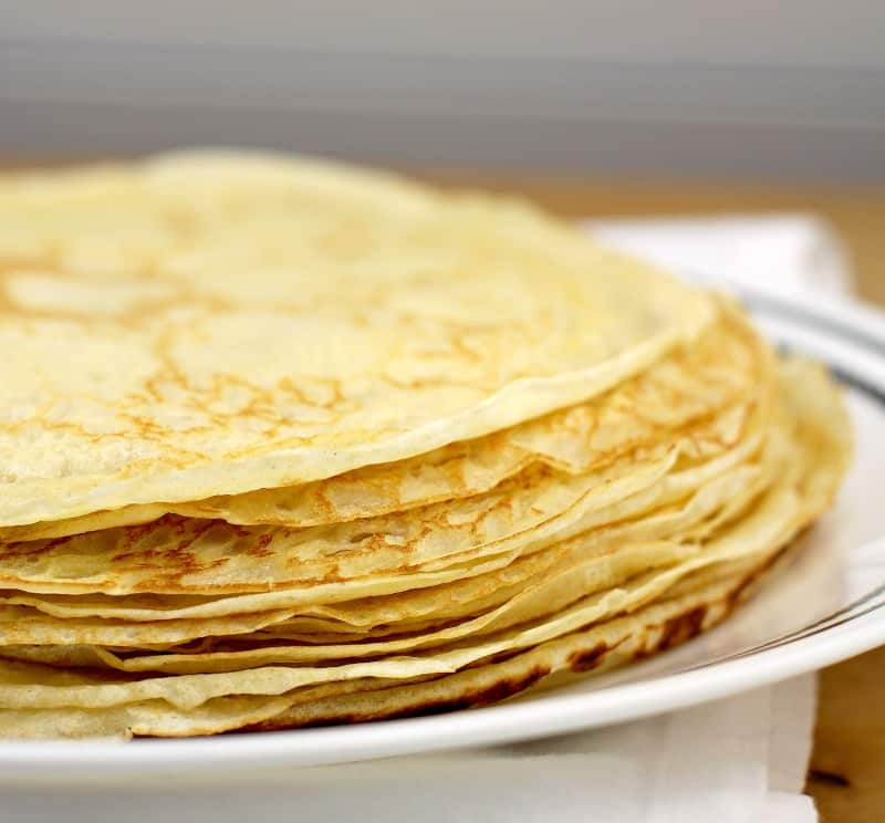 thin crepes in a pile on a white dish, white background