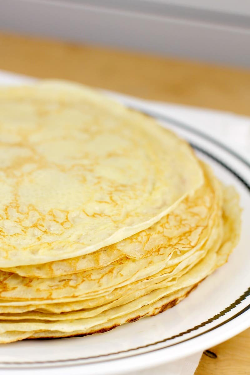 round savory crepes in a stock on a white rimmed dish