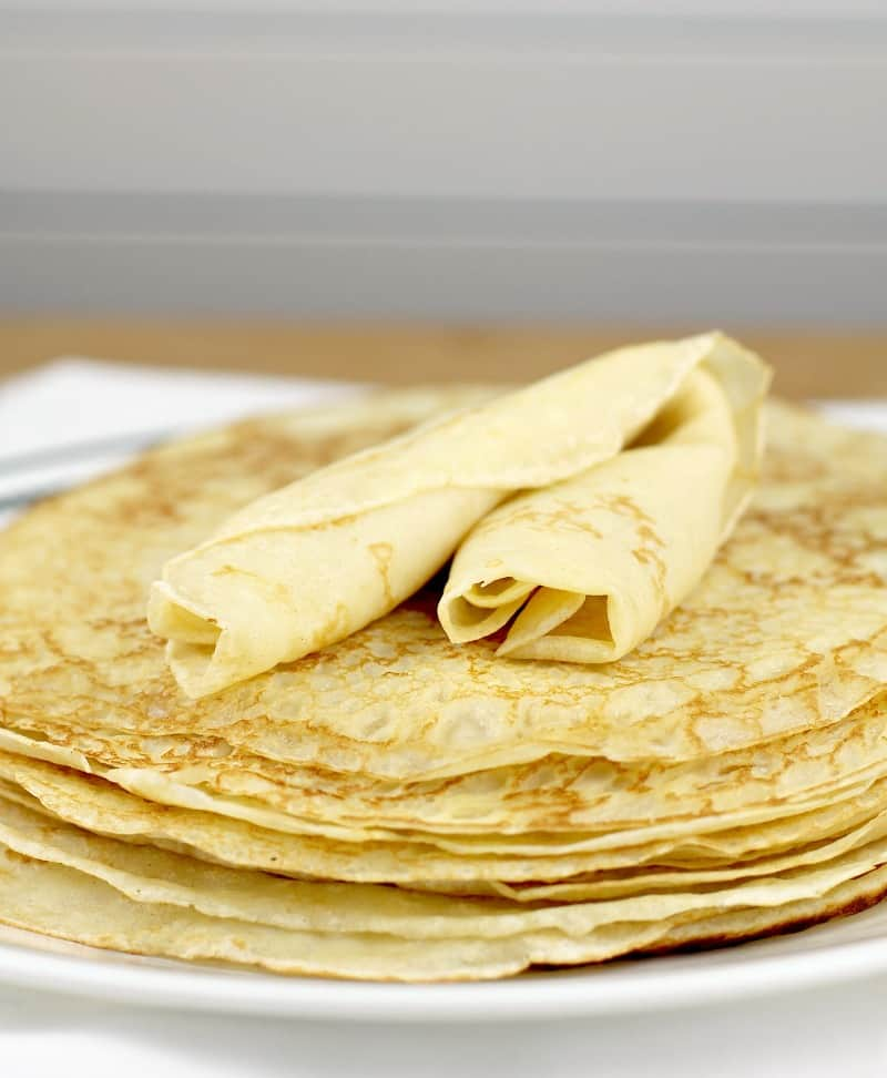stack of crepes with a rolled crepe on top
