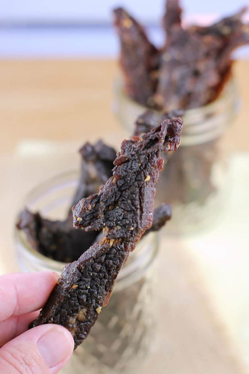hand holding a piece of jerky; mason jars filled with jerky in the background