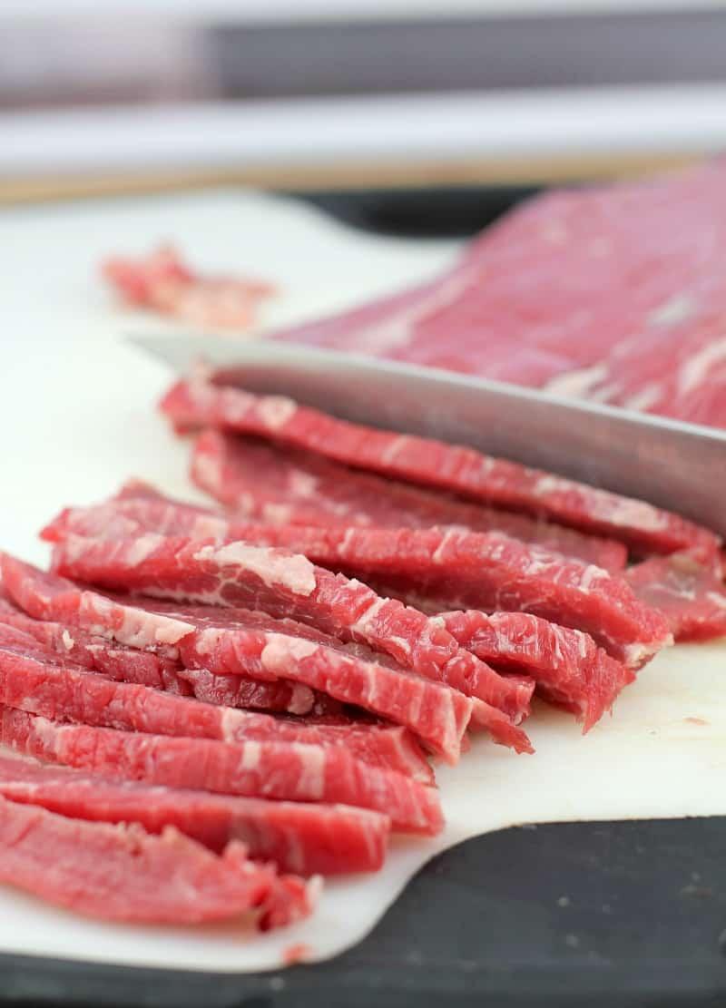 knife slicing flank steak on white board