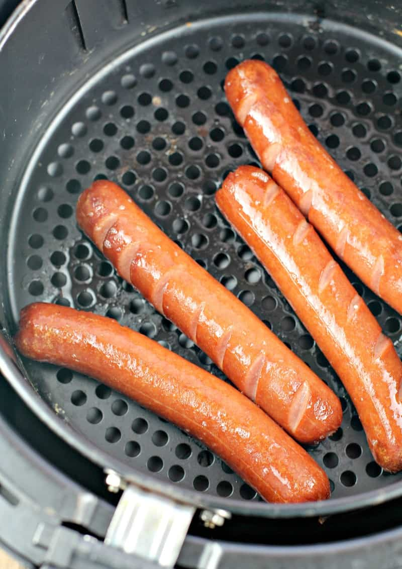 four cooked hot dogs in an air fryer