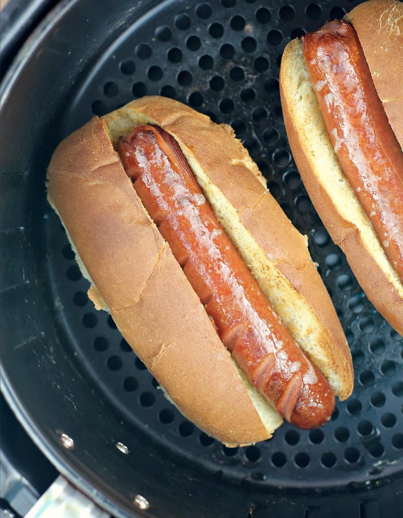 hot dog in a bun in an air fryer basket