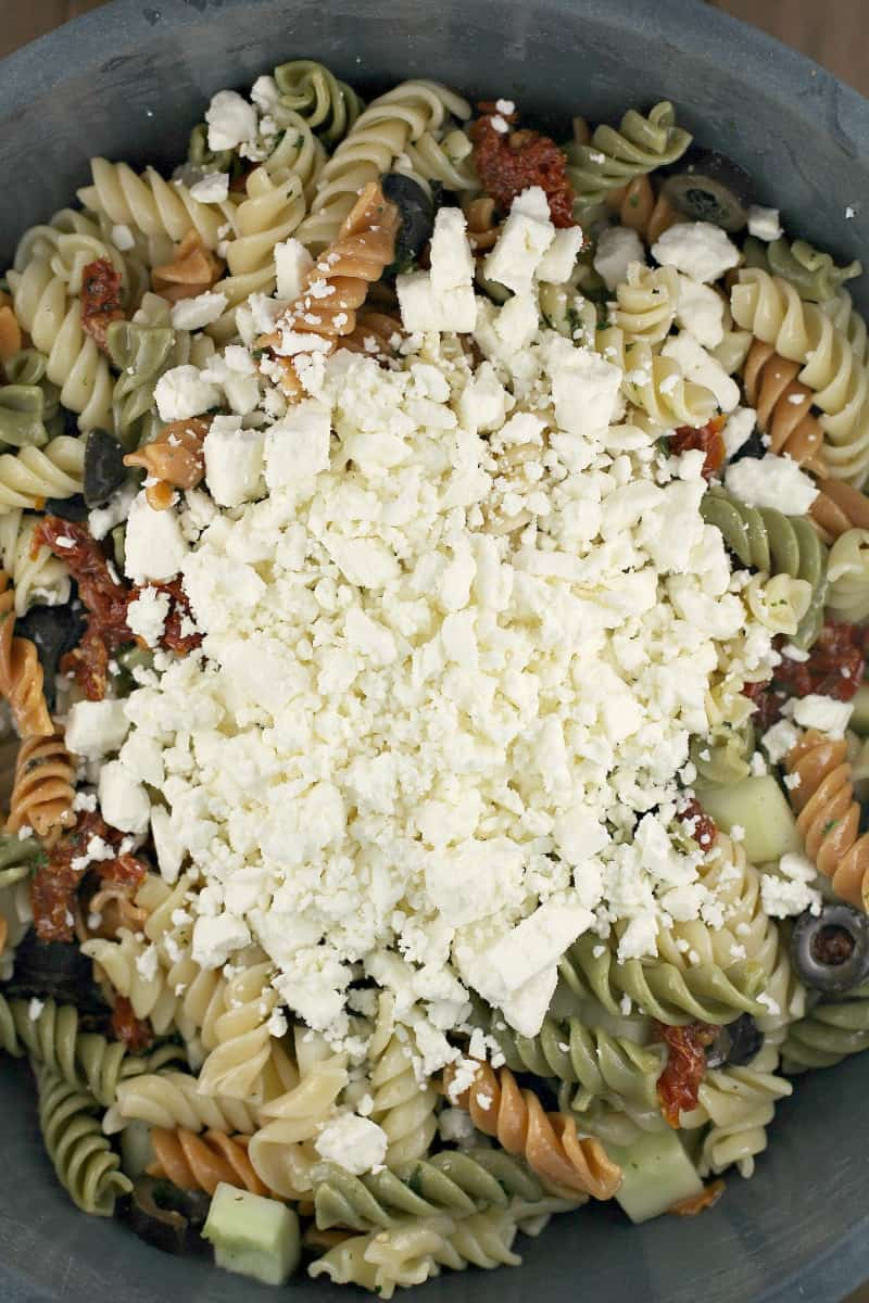 feta cheese on top of pasta salad in a bowl