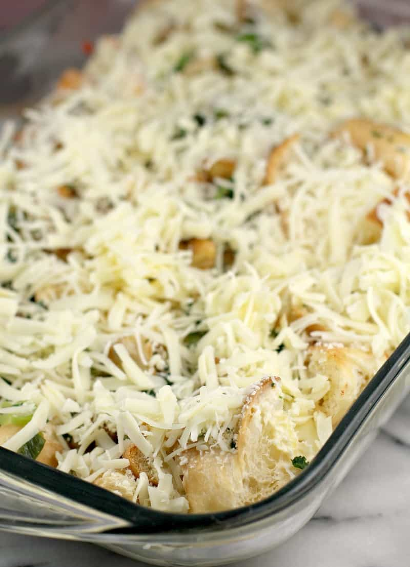 assembled casserole in clear glass bake dish topped with cheese prior to refrigeration and baking