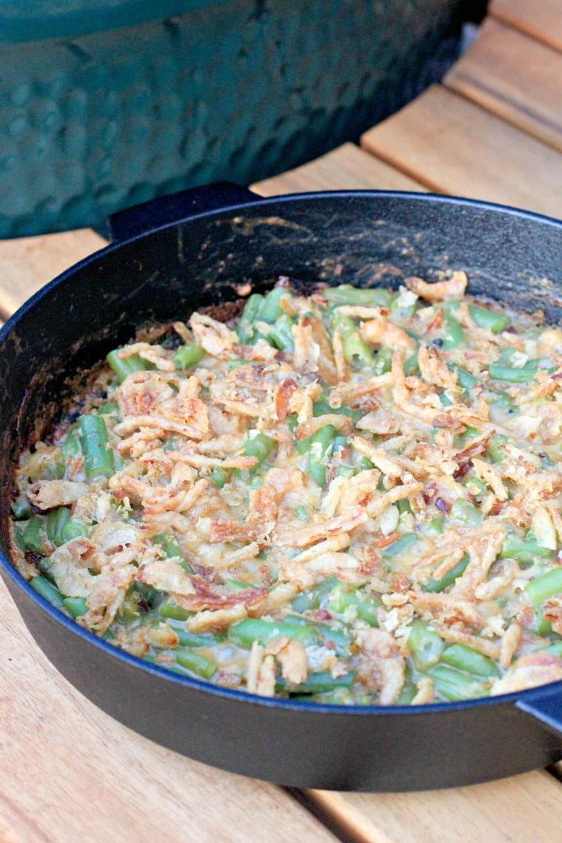 cooked green bean casserole in cast iron skillet on table next to big green egg