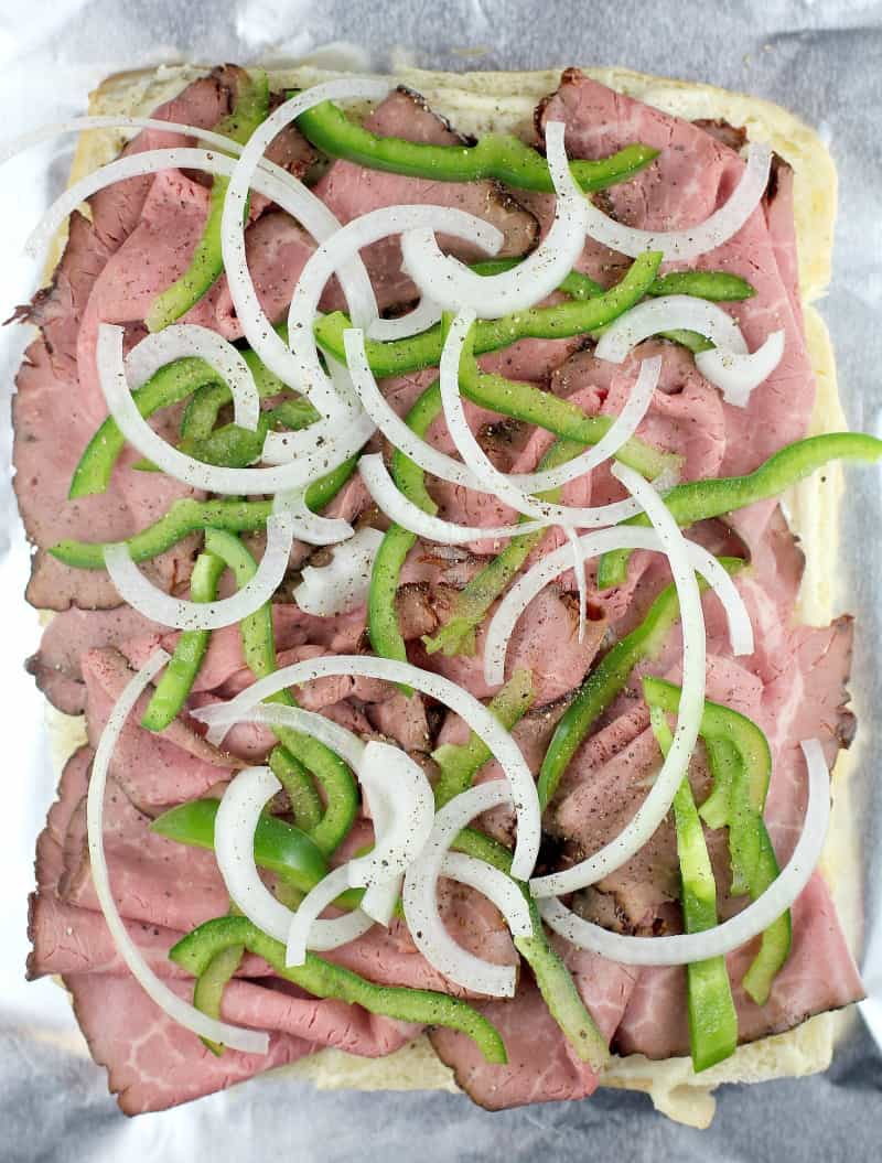 top down view on a half assembled recipe showing the roast beef, onion, and green bell pepper