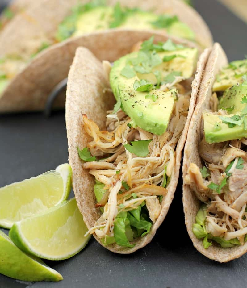2 whole wheat tortillas stuffed with lettuce, chicken, and avocado on a slate with lime wedges
