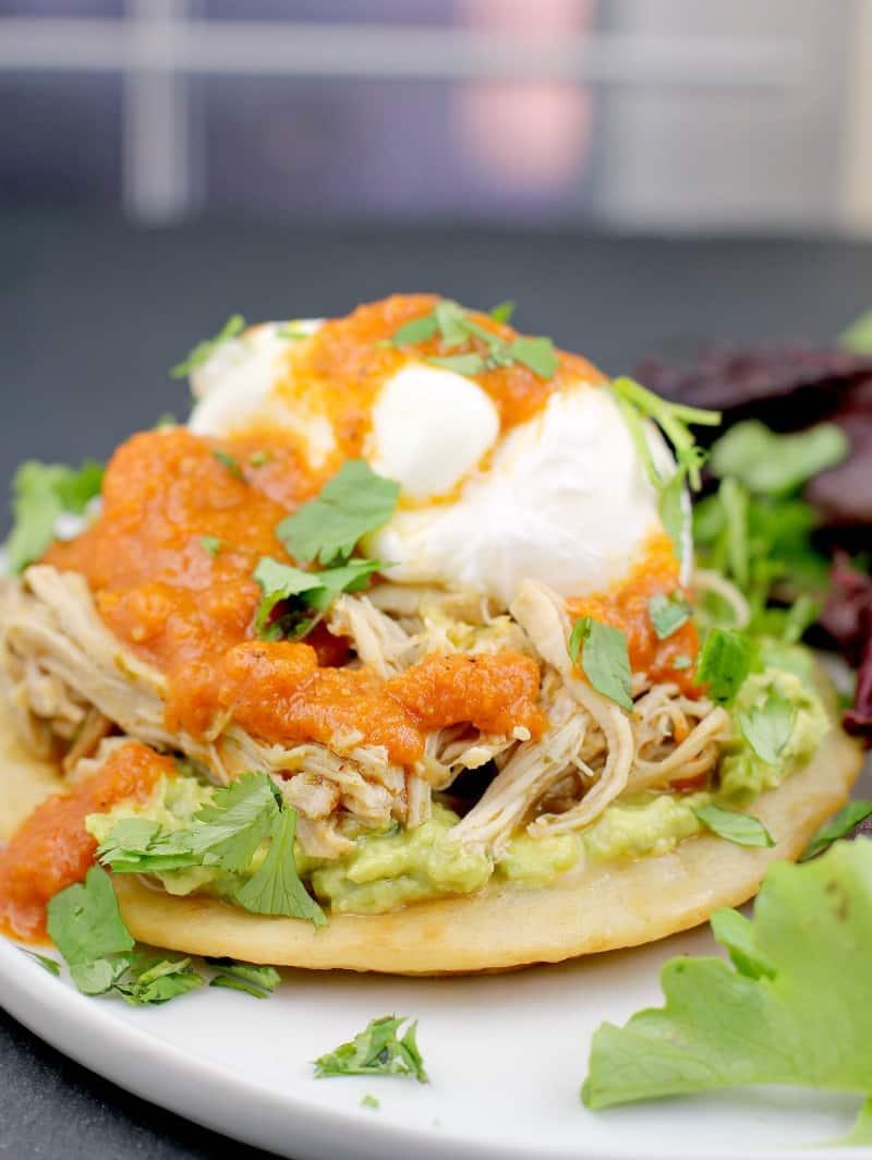 assembled recipe showing a tortilla, guacamole, chicken, egg, and ranchero sauce