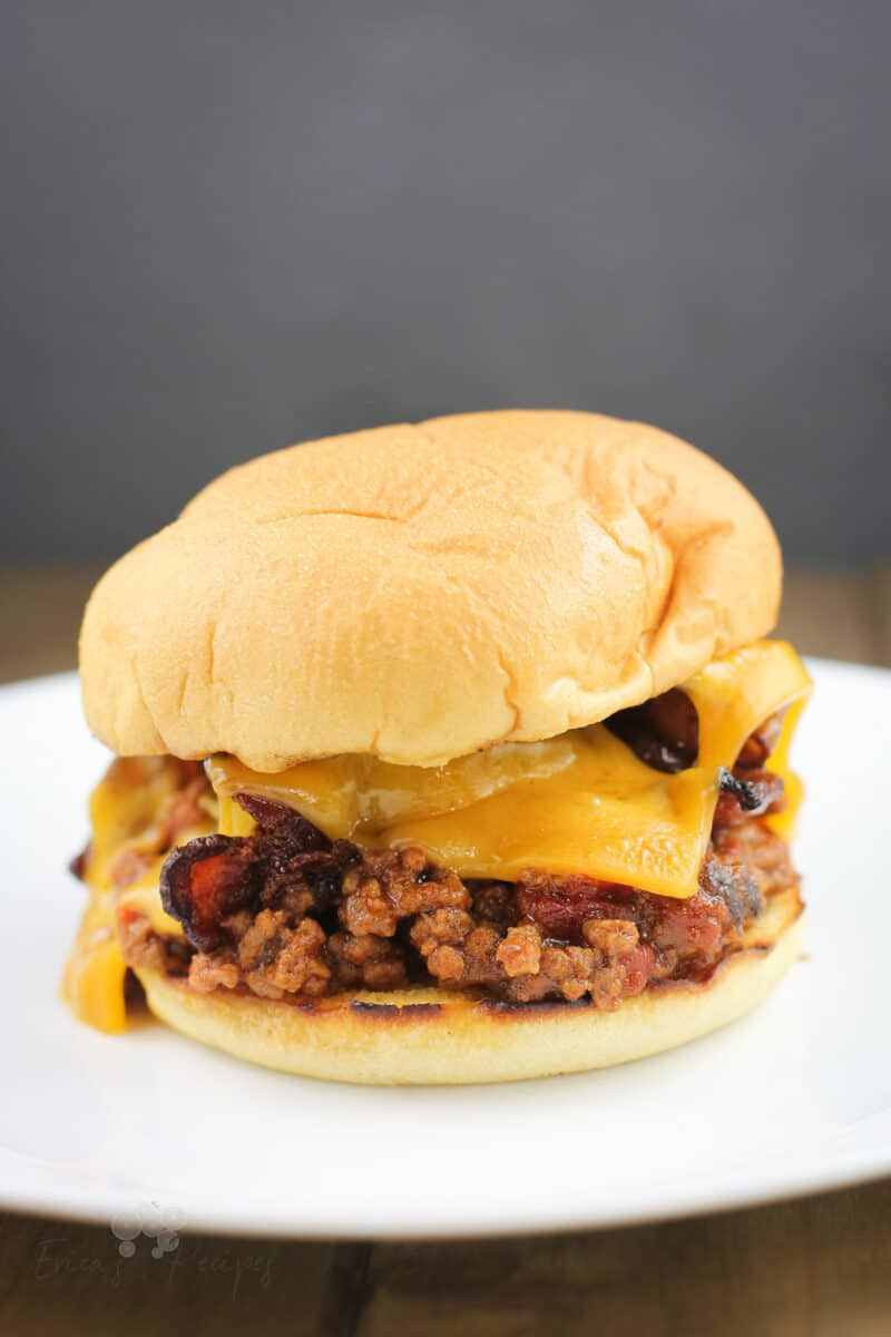 assembled recipe of grilled sloppy joe in a toasted bun with cheddar and bacon; on white plate