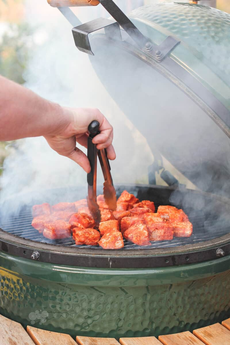 pork belly being placed on grill grate in Big Green Egg