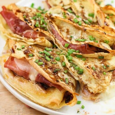 close view of prepared crepes showing prosciutto and melted cheese