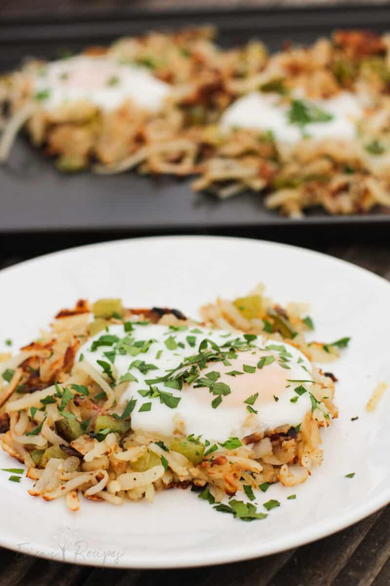 finished recipe on white plate with unbroken egg atop hash browns