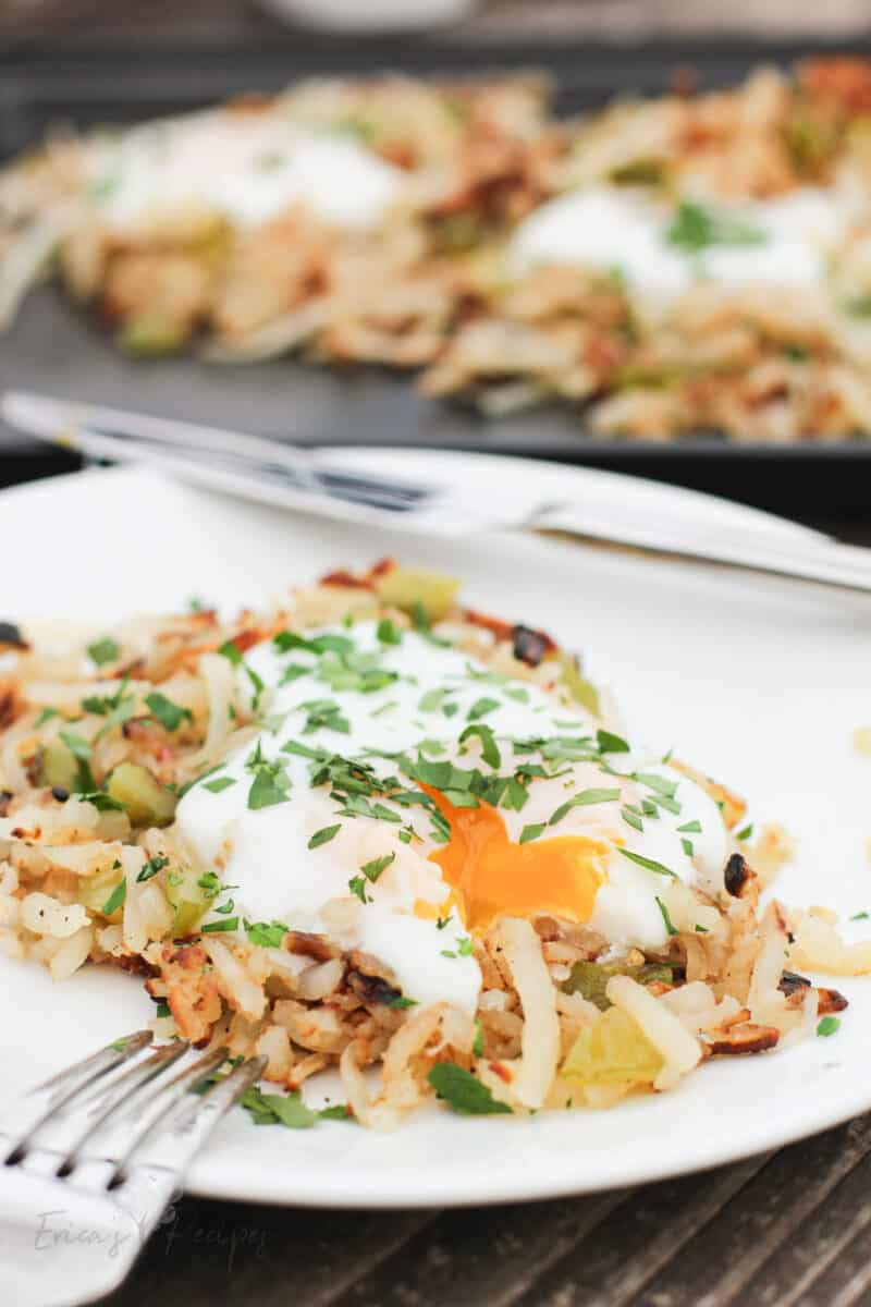 serving of griddle hash browns on white plate with egg broken and yolk running out onto potatoes; rest of potatoes on sheet in background