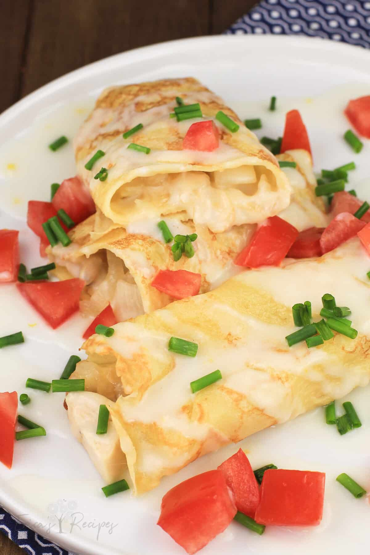 crepes with chicken and potato on white plate, one cut open to show filling