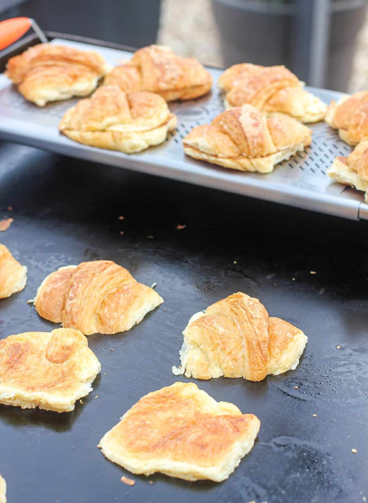 croissants toasting on Blackstone griddle top; warmer rack in the background