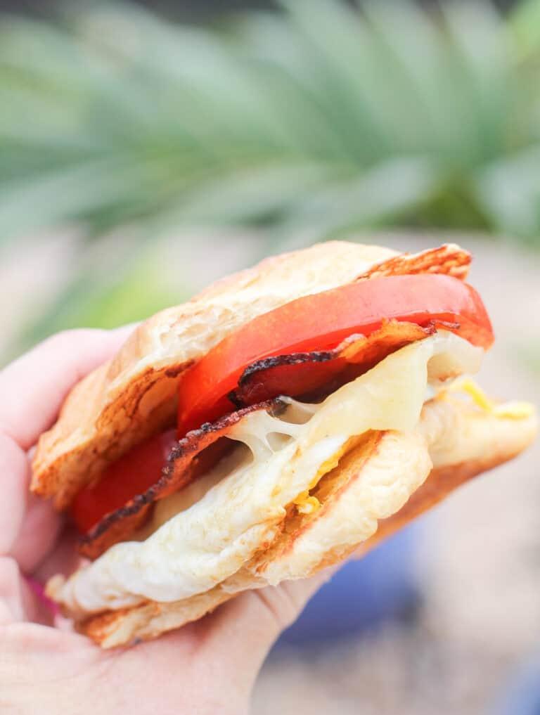 hand holding a croissant breakfast sandwich