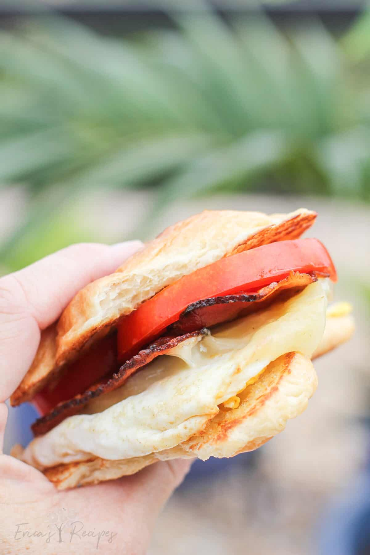 close side view of a hand holding a croissant breakfast sandwich