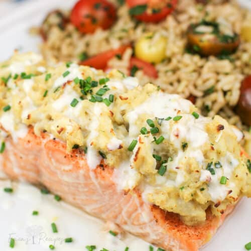 crab stuffed salmon on white plate topped with chives and light lemon sauce. rice with cherry tomatoes in the background