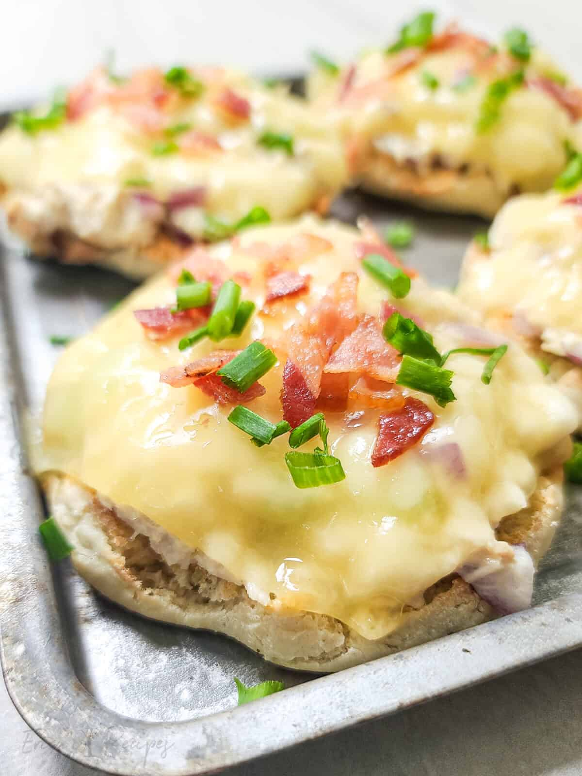 close, side view of open faced tuna melt on bake sheet topped with bacon and chives