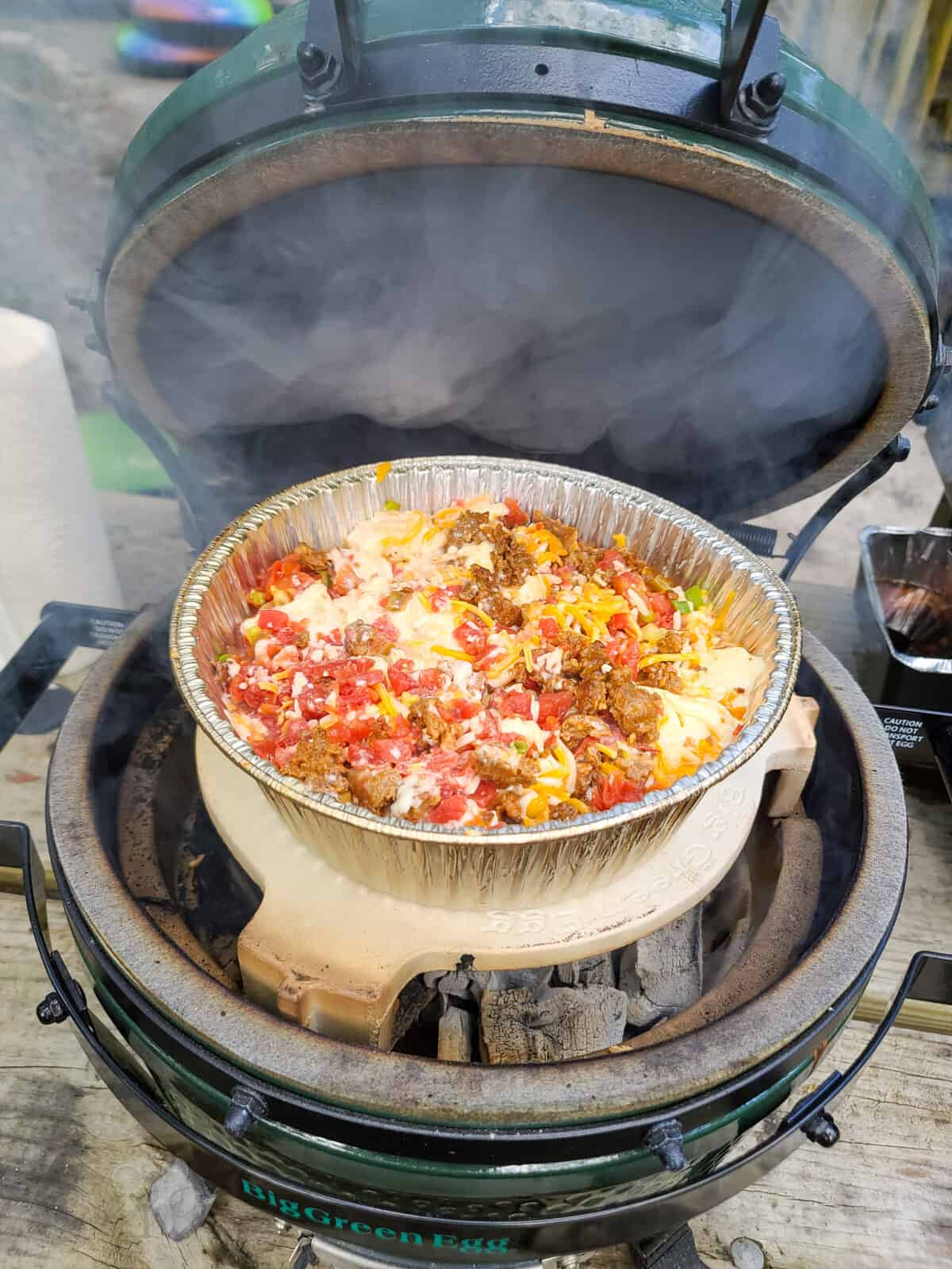 open big green egg with queso smoking on plate setter